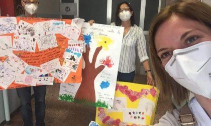 """I bambini abbracciano con dei disegni i """"nonni"""" della casa di riposo dopo l'incendio"""